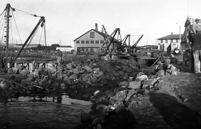 Unnið við flutning á hafnargarðinum árið 1928. Verkamannaskýlið er fyrir miðri mynd. Ljósmyndari Magnús Ólafsson. Ljósmyndasafn Reykjavíkur.